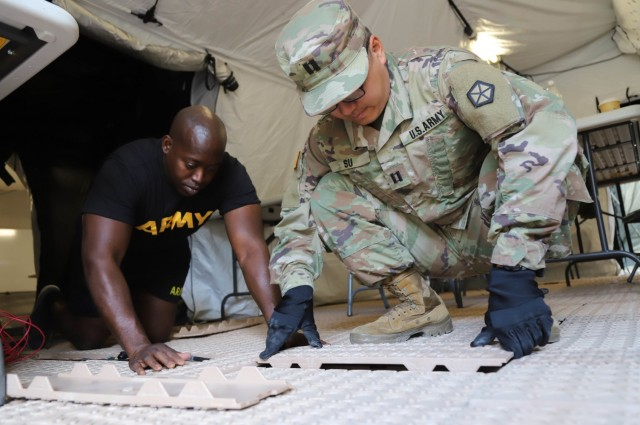 GRAFENWOEHR, Germany - Sgt. 1st Class Allan Triplett (left), Fires support NCO for V Corps, lays flooring with Cpt. Michael Su, a legal officer for V Corps, at the main command post for Warfighter 22-1 in Grafenwoehr, Germany. The WFX 22-1 was V Corps' final certifying exercise in becoming the U.S. Army's fourth corps headquarters and America's forward deployed corps in Europe.(U.S. Army photo by Pvt. Gabriella Sullivan/released)