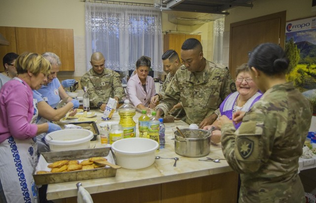U.S. Army Soldiers assigned to the Florida Guard's 50th Regional Support Group, work with members of a local women's organization to prepare traditional Polish dishes at the Powidz Community Center in Powidz, Poland, Oct. 5, 2021. These Soldiers are deployed to Poland with the 50th RSG in support of Atlantic Resolve.