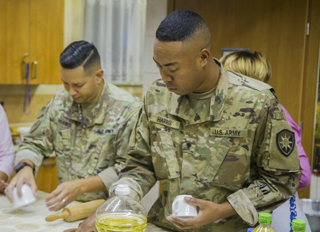 U.S. Army Maj. Joshua Franqui (left), director of intelligence, and Spc. Lamar Harris , intelligence analyst, use cups to cut dough that will be used for making pierogies under the supervision of members of a local women's organization at the Powidz Community Center in Powidz, Poland, Oct. 5, 2021. Franqui and Harris are both deployed with the Florida Guard's 50th Regional Support Group to Poland in support of Atlantic Resolve.