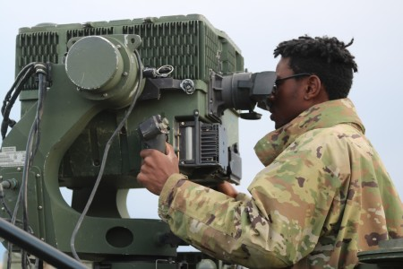 Spc. Caleb Green of 2nd Battalion, 13th Field Artillery Regiment, 1st Stryker Brigade Combat Team, 4th Infantry Division, prepares for his nightly call-for-fire mission with the Long Range Advanced Scout Surveillance System (LRAS) mounted on top of one of his Fire Support Vehicle (Stryker).