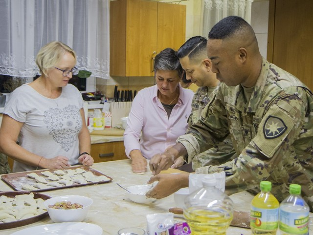 U.S. Army Spc. Lamar Harris (right), an intelligence analyst, and Army Maj. Joshua Franqui, director of intelligence, prepare dough for pierogies under the supervision of Mariola Waszak (left) and Miroslawa Kaluzinska at the Powidz Community Center in Powidz, Poland, Oct. 5, 2021. Harris and Franqui are Soldiers deployed to Poland with the Florida Guard's 50th Regional Support Group in support of Atlantic Resolve. Waszak and Kaluzinska members of a local women's organization.