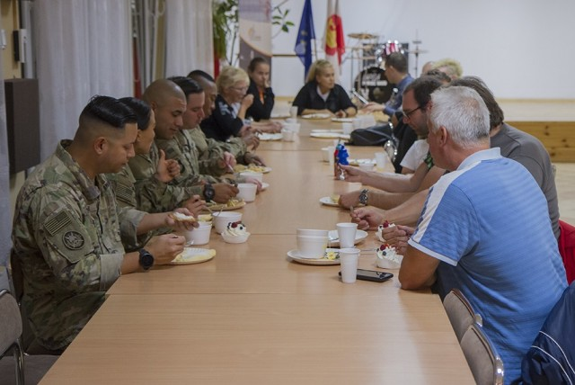 U.S. Army Soldiers assigned to the Florida Guard's 50th Regional Support Group, enjoy a meal with locals after preparing the food with members of a local women's organization at the Powidz Community Center in Powidz, Poland, Oct. 5, 2021. They are deployed to Poland with the 50th RSG in support of Atlantic Resolve.
