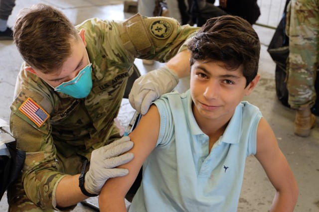 Pvt. Hayden McClure, an Army medic assigned to 1st Squadron, 2nd Cavalry Regiment, administers an MMR vaccine to an Afghan evacuee at Rhine Ordnance Barracks, Germany, Sept. 18. A diverse team of Army medical professionals vaccinated nearly 5,500 Afghan evacuees in less than 72 hours at ROB to protect them from the diseases and to help ensure the health and well-being of the military and local communities.