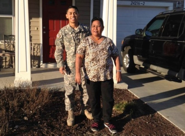 """Staff Sgt. Welington E. David, an automated logistics specialist assigned to the 264th Combat Support Sustainment Battalion, 3rd Infantry Division Sustainment Brigade, 1st Theater Sustainment Command, poses with his mother, Valentina Elewel, in a photo family from the past. """"My inspiration really was my mom, [she took] care of me 18 years of my life, and so it was my way of tribute and of paying her back for all the hardship that she has gone through just to be able to get me to where I am today,"""" David said. (Photo courtesy of Staff Sgt. Welington E. David)"""