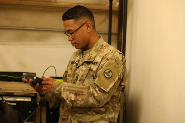 """Staff Sgt. Welington E. David, an automated logistics specialist assigned to the 264th Combat Support Sustainment Battalion, 3rd Infantry Division Sustainment Brigade, 1st Theater Sustainment Command, troubleshoots an issue on a system he uses to manage logistics in Jordan and Iraq, on Oct. 9, 2021, at Camp Buehring, Kuwait. """"I didn't want to stay stagnant and wait for an opportunity to come to me, I had to go out and find that opportunity,"""" David said. (U.S. Army photo by Spc. Elorina Santos)"""