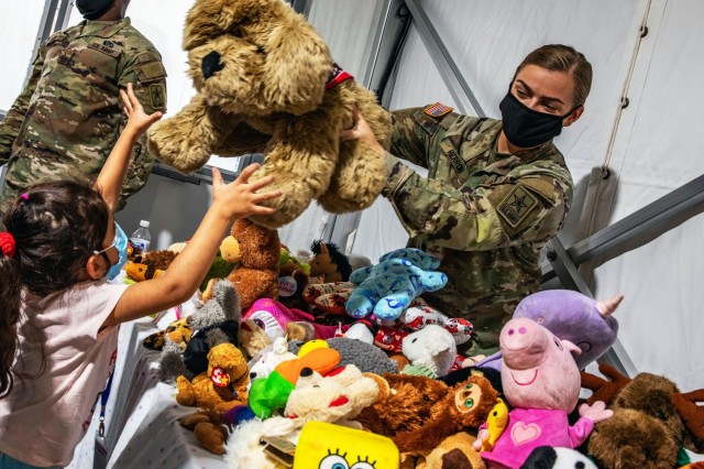 Army Pvt. 1st Class Kylee Herron hands a stuffed dog to an Afghan child during a toy giveaway at Fort Lee, Va., Sept. 15, 2021.