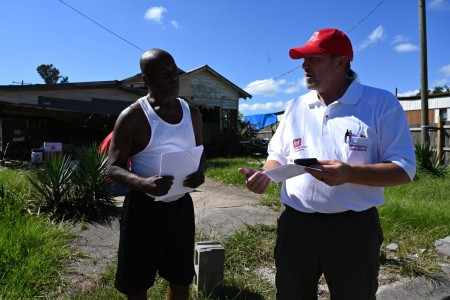 Dereck Wansing, right, a U.S. Army Corps of Engineers, Kansas City District engineering technician and local government liaison supporting Hurricane Ida recovery efforts in Louisiana, discusses the Operation Blue Roof process to a homeowner in Houma, Louisiana, Oct. 12.